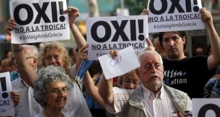 People hold signs supporting Greece during a pro-Greece protest in front of European Union office in Barcelona, Spain
