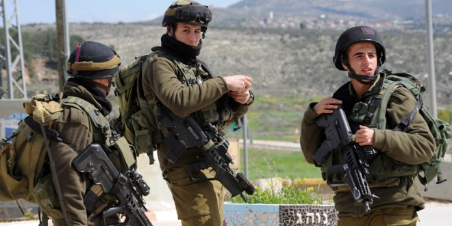 Israeli soldiers guard the road to the Israeli settlement Itamar where five family members were killed by a Palestinian late Friday night