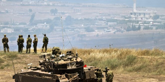 Israeli soldiers stand near a Merkava tank stationed in the Israeli annexed Golan Heights near the Quneitra crossing with Syria (background) on July 16, 2013. Mortar fire from inside war-torn Syria hit the Israeli-occupied Golan Heights causing several wildfires to break out along the ceasefire line, an AFP correspondent reported. The apparently stray rounds struck as Syrian rebels and regime forces battled near Quneitra which lies in no-man's land, the correspondent reported. AFP PHOTO / JACK GUEZ